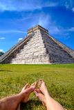 Pyramid Castillo in Chichen itza and relaxing legs on grass Royalty Free Stock Images