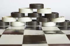 Pyramid checkers on chessboard. The pyramid of the checkers on the chessboard Royalty Free Stock Photos