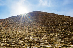 The pyramid of Cheops in Giza on the background of the Sun,Cairo. The pyramid of Cheops in Giza in the sunny day, Cairo, Egypt Stock Photos