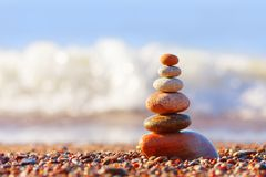 Concept of harmony and balance. Evening calm. Pyramid of colorful, balanced stones on the sea background. Concept of harmony and balance. Soft focus, selective Stock Images