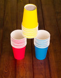 Pyramid of colorful disposable paper cups on background dark wood. Stock Photography