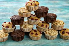 Pyramid of colorful muffins with chocolate, cherry and almonds on table. stock photos