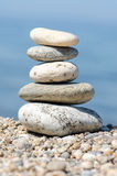 Pyramid of colorful pebbles . Rock Zen in the background of the sea. Concept of harmony and balance. Stock Photos