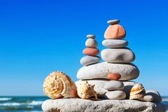 Pyramid of colorful rocks and shells on the sea background. The Stock Photography