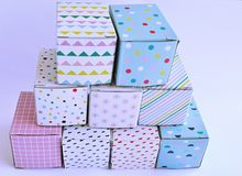 Pyramid of colourful cardboard boxes on white background. Stack of nine colourful and patterned cardboard boxes in a pyramid on a white background Stock Photo