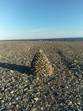 The pyramid is composed of pebbles of the beach on the seafront stock image