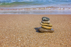 Pyramid from flat stones on a sandy beach. Near the sea Royalty Free Stock Photos