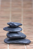 Pyramid of four stones. On bamboo mat Royalty Free Stock Images