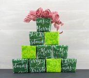 Pyramid of Gifts with Red and White Curly Ribbon. Against White Wood Textured Background Stock Image