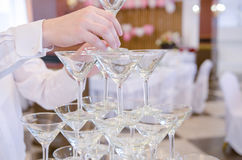 Pyramid of glasses of champagne for celebrate. Waiter hand with glass of champagne over pyramid during catering at party Royalty Free Stock Photos