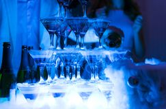 Pyramid of glasses with champagne in dark blue color, alcohol, p. Arty, drink, bottle, dry ice, smoke royalty free stock image