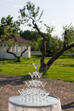 Pyramid of glasses for champagne at outdoor garden in wedding ceremony. Royalty Free Stock Image