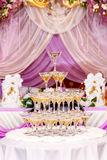 Pyramid of glasses with champagne in purple wedding interior. Stock Photos
