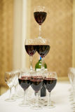 Pyramid of glasses with red wine stock images