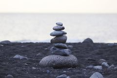 Pyramid of gray stones on the background of the ocean on the beach with black sand in Portugal. royalty free stock image