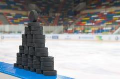 The pyramid of hockey pucks. MOSCOW - JANUARY 28: The pyramid of hockey pucks before playing in the KHL regular Hockey match Dynamo (Moscow) - Slovan (Bratislava Stock Photos
