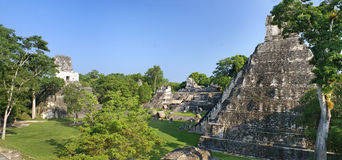 Pyramid and houses in the Mayan city-state of Tikal Stock Photo