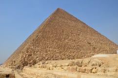 Pyramid i sanddamm under gråa moln Arkivbild