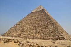 Pyramid i sanddamm under gråa moln Arkivbilder