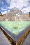 The Pyramid of Louvre. Paris, France. PARIS - JUNE 06: Vertical oriented image of famous glass Pyramid and beautiful fountain. Pyramid  is popular touristic Royalty Free Stock Photo