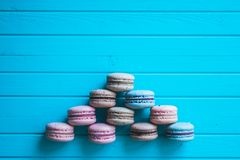 Pyramid macaroons or macaron lie on a turquoise wooden background, top view, copy space.  Royalty Free Stock Photography