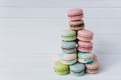 Pyramid of macaroons or macaron on a white wooden background. Almond cookies, copy space. Pyramid of macaroons or macaron on a white wooden background. Almond Royalty Free Stock Image