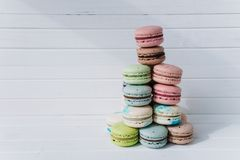 Pyramid of macaroons or macaron on a white wooden background. Almond cookies on a desk, copy space. Pyramid of macaroons or macaron on a white wooden background Stock Photography