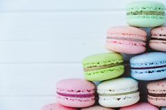 Pyramid of macaroons on a white wooden background close-up, copy space.  Stock Image