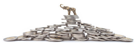 Pyramid made with many coins with lucky elephant Royalty Free Stock Photos