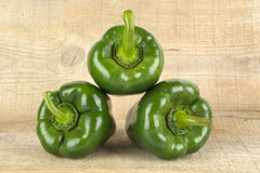 Pyramid made of three green bell peppers on wooden plank Royalty Free Stock Image