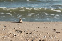 Pyramid is made of white stones against the background of sea waves. stock photos
