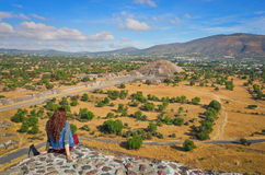 Pyramid of the Moon and the road of death in Teotihuacan. Young woman sitting on the top of pyramid in Teotihuacan. View of Pyramid of the Moon and the road of stock images