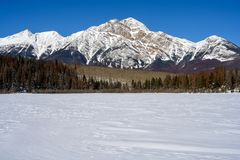 Pyramid Mountain and the frozen Patricia Lake in the Jasper National Park Alberta, Canada. Winter landscape of the Pyramid Mountain with the frozen Patricia Lake stock images