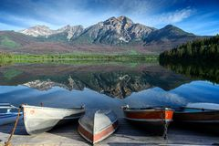 Pyramid Mountain reflecting in the Patricia Lake in the Jasper National Park Alberta, Canada. The Patricia Lake with some boat at the lakeshore ready for summer royalty free stock images