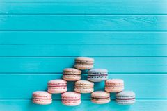 Pyramid of multicolored macaron or macaroons lie on a turquoise wooden background, almond cookies in pastel tones, top. View, copy space Stock Images