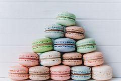 Pyramid of multicolored macarons or macaroons on a white wooden background, almond pastel tones.  Royalty Free Stock Image