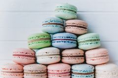 Pyramid of multicolored macaroons on a white wooden background, almond cookies in pastel tones close-up.  Royalty Free Stock Image