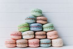Pyramid of multicolored macaroons on a white wooden background, almond cookies in pastel tones.  Royalty Free Stock Images