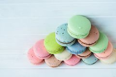 Pyramid of multicolored macaroons on a white wooden background, almond cookies in pastel tones. Top view, copy space.  Stock Photography