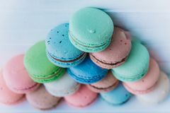 Pyramid of multicolored macaroons on a white wooden background, almond cookies in pastel tones. Top view. Pyramid of multicolored macaroons on a white wooden Royalty Free Stock Photos
