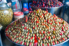 Pyramid of olives. Pyramidal heap of green olives and red pepper in a Sicilian public market Stock Photo