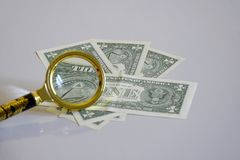 Pyramid of one-dollar banknote inside a magnifying glass royalty free stock images