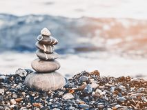 Pyramid of pebbles on the beach.Waves in background. Retro style. Pyramid of pebbles on the beach.Waves in background stock image