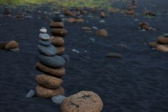 Pyramid of pebbles on black volcanic beach in Iceland Stock Photos