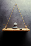 Pyramid of pebbles on the old wood shelf stock image