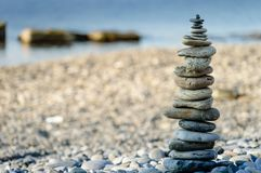Pyramid of sea stones on pebbles of the sea shore. The concept of balance and spirituality. Stock Photos