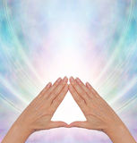 Pyramid Power Energy Healing. Female hands making a triangle shape on a misty blue flowing triangular shaped energy field with plenty of copy space above Stock Photography