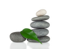 The pyramid of round stones with green leaf Royalty Free Stock Image