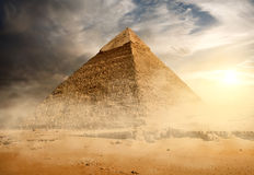Pyramid in sand dust. Under gray clouds royalty free stock photos