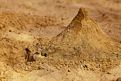 A pyramid of sand in the sandbox. A pyramid of sand in the children's sandbox Royalty Free Stock Image
